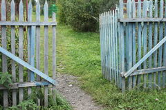A blue old ragged gate to a dacha garden in a village with ground and grass and trees Royalty Free Stock Photo