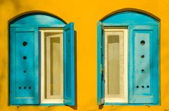 Blue old style wooden windows, symmetry in open doors, yellow house wall background in small town, minimal style of simplicity,. Trendy look, contrast bright royalty free stock images