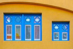 Blue old style wooden windows, symmetry in open doors, yellow house wall background in small town, minimal style of simplicity,. Trendy look, contrast bright royalty free stock photo