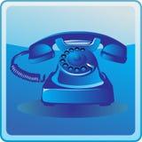 Blue old telephone. On blue background Stock Photos