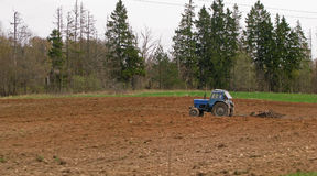 Blue old tractor on the field. Plowing the brown soil Stock Photography
