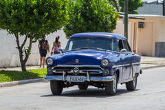 Blue Oldtimer drive on the street in the countryside from Cuba Stock Photo