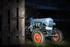 Blue oldtimer farming tractor standing next to a w Stock Photo