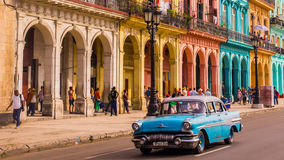 Blue oldtimer taxi in Havana, Cuba. Havana, Cuba on December 22, 2015: A blue oldtimer taxi is driving through Habana Vieja in front of a colorful facade Royalty Free Stock Photo