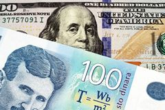 A blue one hundred Serbian dinar bank note with an American one hundred dollar bill. A close up image of a blue one hundred Serbian dinar bank note with an royalty free stock image
