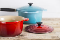 Blue and open red saucepans Stock Photos