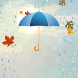 Blue opened umbrella with rain and falling leaves Stock Photos