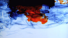 Blue orange and black ink swirling in water stock video footage