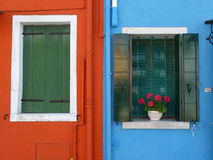 Blue orange colorful building with green window in Burano Italy. Build in burano venice Italy Europe colorful painting flower on green window royalty free stock photo