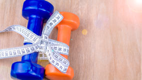 Blue and orange dumbbells bound together with centimetric tape as gift on wooden background Royalty Free Stock Photo