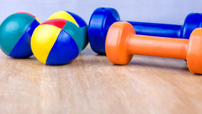 Blue and orange dumbbells and coloured balls on wooden surface Stock Photos