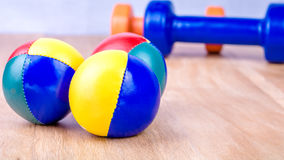 Blue and orange dumbbells and coloured balls on wooden surface Stock Images