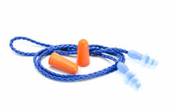 Blue and orange earplugs with a string on white background. Royalty Free Stock Images