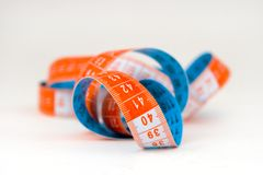 Blue and orange  measuring tape. Blue and orange spiral  measuring tape over white Stock Photo