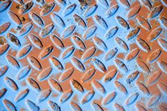 Blue and orange metal grate. Textured manhole cover with a coat of blue and orange paint stock images