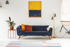 Blue and orange painting hanging on a white wall above an elegant sofa with decorative cushions in living room interior. Real stock images