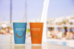 Blue  and orange  paper coffee cup with straws and enjoy sign Royalty Free Stock Image