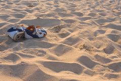 Blue-orange sandals on a sandy ocean beach royalty free stock image