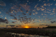 Blue and Orange Scenic Sunset on the Texas Plains. With Reflective Creek and Small Clouds Royalty Free Stock Image