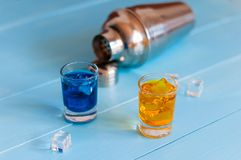 Blue and orange shots near metal sheker on wooden Stock Photos