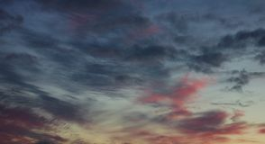 Blue and orange sky with wavy blue and pink sunset clouds royalty free stock photography