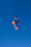 Blue And Orange Snowboarder Mid Air. Snowboarder competing in competition in Val Thoren, France stock image