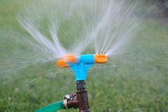 Blue and orange sprinkler watering grass. Garden irrigation system watering lawn. Closeup image of a garden sprinkler on Royalty Free Stock Photography