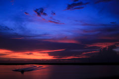 Blue and orange sunset. A blue and orange sunset with a boat and waves Royalty Free Stock Image