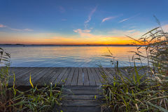 Blue and Orange Sunset over Boardwalk on the shore of a Lake Stock Photo