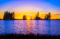 Blue and Orange Sunset over Lake With Tree Silhouettes Stock Images