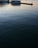 Blue and Orange Water at Sunset with a Dock. Water ripples near a dock at sunset Royalty Free Stock Image