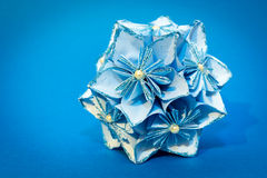 Blue origami flower ball on the blue background.  stock photo