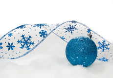 Blue ornament. Blue ribbon and ornament on the snow Royalty Free Stock Photos
