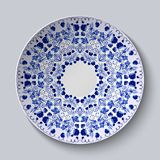 Blue ornament of berries and flowers. Pattern is applied on a ceramic plate. Stock Photo