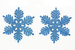 Blue ornamental snowflakes. Two identical blue ornamental snowflakes, isolated on a white background royalty free stock image