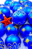 Blue Ornaments with Red Star. Different Christmas ornaments over a soft white background Royalty Free Stock Image