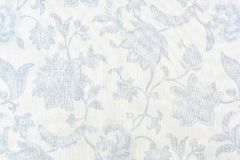 Blue ornate floral pattern on white cotton tablecloth. Background royalty free stock photo