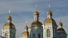 Blue orthodox church with golden domes and crosses against a blue sky. A blue orthodox church with golden domes and crosses against a blue sky stock video