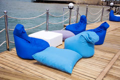 Blue pillows on a wooden pier .Lounge area. Blue outdoor furniture for relaxation royalty free stock image