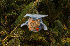 Blue Owl Ornament. A knitted owl ornament hangs in a gently lit Christmas tree stock photos