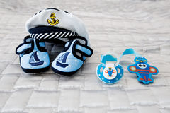 Blue pacifier, sailor hat, baby bootees Stock Images