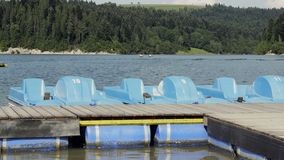 Blue paddle boat. Water pedal boats parked at small pier. Summer vacation scenery by beautiful lake stock video footage