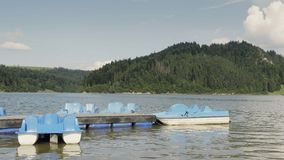Blue paddle boat. Water pedal boats parked at small pier. Summer vacation scenery by beautiful lake stock video