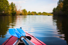 Blue paddle lying on kayak. Kayaking in a river. Summer sunny sport day in outdoor with beautiful nature Royalty Free Stock Photo