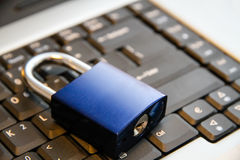 Internet and computer systems security concept: blue padlock closed on top of laptop computer keyboard Royalty Free Stock Photography