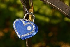 Blue padlock in the form of a heart on iron bars Royalty Free Stock Photo