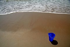 Blue pail on the beach. Blue pail in the sand on the beach with a wave approaching stock photography