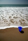 Blue pail on the beach. Blue pail in the sand on the beach with a wave approaching royalty free stock images