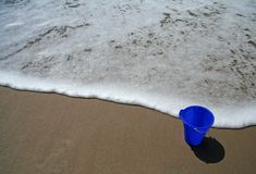 Blue pail on the beach. Blue pail in the sand on the beach with a wave approaching stock images