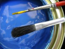 Blue Paint. Detail of blue paint can with two brushes on top Stock Photo